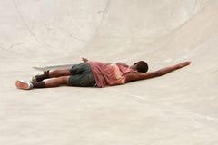 L'adolescent s'étend sur le béton après élimination pendant la course de planche à roulettes Photographie stock libre de droits