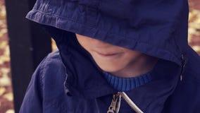L'adolescent sans abri dans une veste avec un capot bleu a abaissé sa tête, un petit garçon attend une solution Aidez photographie stock libre de droits