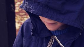 L'adolescent sans abri dans une veste avec un capot bleu a abaissé sa tête, un petit garçon attend une solution Aidez photos libres de droits