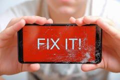L'adolescent se tient dans le périphérique mobile de mains avec l'écran tactile cassé photo libre de droits