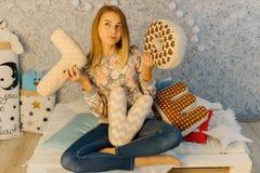 L'adolescent throughtful tient les coussins avec des lettres d'amour et s'assied sur le sofa Photo stock
