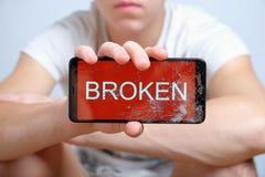 L'adolescent tient le périphérique mobile disponible avec l'écran tactile cassé photos libres de droits