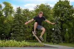 L'adolescent a tiré dans le ciel sur une planche à roulettes en parc de patin Photographie stock libre de droits