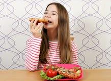 L'adolescente affamato mangia il panino immagini stock