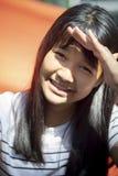 L'adolescente asiatico della pelle di Tan facendo uso della mano protegge il sole bruciato sul fronte SK fotografia stock