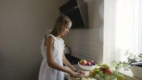 L'adolescente attraente in vestito bianco sta preparando la macedonia di frutta nella cucina La ragazza cosciente in buona salute video d archivio