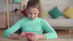 L'adolescente avec un d?faut facial utilise un smartphone se reposant ? la table ? la maison banque de vidéos