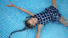 L'adolescente avec un tresse se situe sur elle de retour dans l'eau dans un petit juste de piscine dans des ses vêtements Vacance banque de vidéos