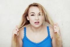L'adolescente biondo della donna che la mostra ha danneggiato i capelli asciutti Fotografie Stock