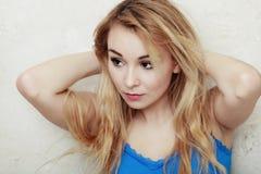 L'adolescente biondo della donna che la mostra ha danneggiato i capelli asciutti Immagine Stock
