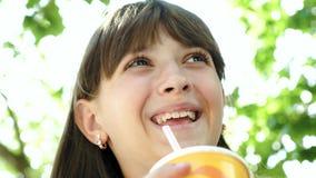 L'adolescente boit le cocktail de la paille et les sourires marchent autour de la ville Plan rapproché banque de vidéos