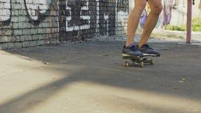 L'adolescente che salta sul pattino e sulla guida, tenenti l'equilibrio, hobby della gioventù stock footage
