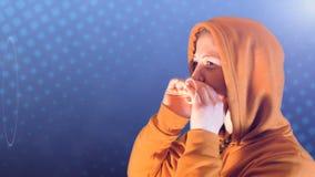 L'adolescente, con la maglia con cappuccio e la maglietta felpata arancio, grida le onde sonore, metraggio ideale per rappresenta stock footage