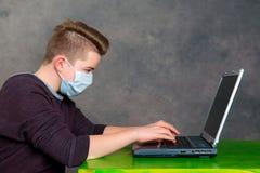 L'adolescente con la maschera chirurgica protegge il computer dal virus Fotografia Stock Libera da Diritti