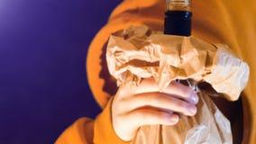 L'adolescente dans le pull molletonné à capuchon orange boit une bouteille alcoolique superbe enveloppée dans un sac de papier banque de vidéos