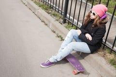 L'adolescente dans les jeans et des lunettes de soleil s'assied sur la planche à roulettes Photos stock