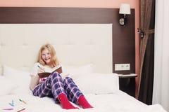 L'adolescente de fille dessine dans le lit Photographie stock libre de droits