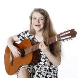 L'adolescente de sourire dans la robe joue la guitare dans le studio Photos stock