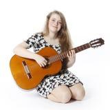L'adolescente de sourire dans la robe joue la guitare dans studiositting Image stock