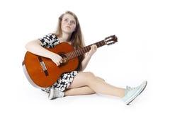 L'adolescente de sourire dans la robe joue la guitare se reposant sur la Floride Image stock