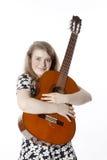 L'adolescente de sourire dans la robe tient la guitare dans le studio Photographie stock