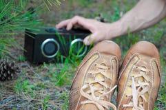 L'adolescente dei pantaloni a vita bassa si rilassa sulla terra e sulla musica d'ascolto nel parco verde del sammer Fotografia Stock