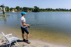 L'adolescente del ragazzo sta pescando sulla canna da pesca di estate fotografia stock