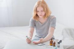 L'adolescente della ragazza misura il livello della glicemia immagini stock