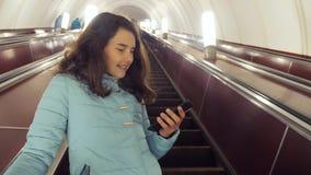 L'adolescente della ragazza nel sottopassaggio sotterraneo guida su una scala mobile, tiene lo smartphone ricerca castana della f video d archivio