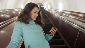 L'adolescente della ragazza nel sottopassaggio sotterraneo guida su una scala mobile, tiene lo smartphone ricerca castana della f archivi video