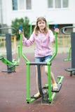 L'adolescente est engagée chez l'équipement d'exercice du ` s des enfants Images stock