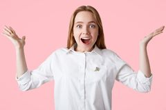 L'adolescente estatico gestures con le mani, esclama con felicità, essendo nel buon umore come riceve notizie positive dal compag fotografia stock