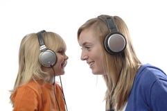 L'adolescente et l'enfant en bas âge écoutent musique Photographie stock libre de droits
