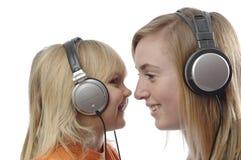 L'adolescente et l'enfant en bas âge écoutent musique Photo stock