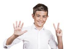 L'adolescente felice che mostra sette dita, numera il gesto 7 Fotografia Stock