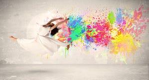 L'adolescente felice che salta con l'inchiostro variopinto schizza sul backg urbano Fotografia Stock Libera da Diritti
