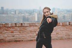 L'adolescente felice con le cuffie gode di di ascoltare la musica ed il ballo Fotografie Stock Libere da Diritti