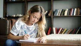 L'adolescente grazioso scrive una lettera in taccuino al primo piano della scuola archivi video