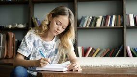 L'adolescente grazioso scrive una lettera in taccuino al primo piano della scuola video d archivio