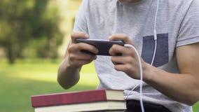 L'adolescente ha messo da parte i libri con compito per giocare il video gioco, concetto di dipendenza archivi video