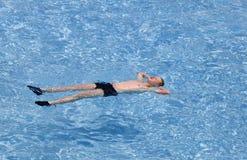 L'adolescente ha un resto sull'acqua trasparente del turchese Fotografie Stock Libere da Diritti