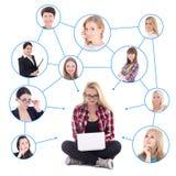 L'adolescente heureuse avec l'ordinateur portable et son réseau social a isolé o Photographie stock