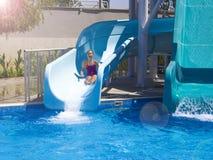 L'adolescente heureuse descendant par l'eau glissent dans la piscine images stock