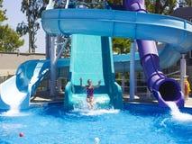 L'adolescente heureuse descendant par l'eau glissent dans la piscine photo libre de droits