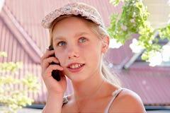 L'adolescente heureuse parle au téléphone Image stock