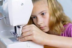 L'adolescente insère soigneusement le fil dans l'aiguille Photographie stock