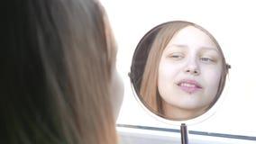 L'adolescente modèle de beauté regardant dans le miroir et vérifiant sa peau, s'appliquant composent 4K clips vidéos