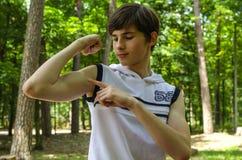L'adolescente mostra il bicipite sulle sue mani immagine stock