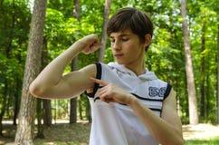 L'adolescente mostra il bicipite sulle sue mani immagine stock libera da diritti