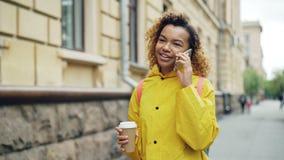 L'adolescente razza mista allegro sta parlando sullo Smart Phone e tenendo elimini il caffè che cammina lungo la via in bello video d archivio